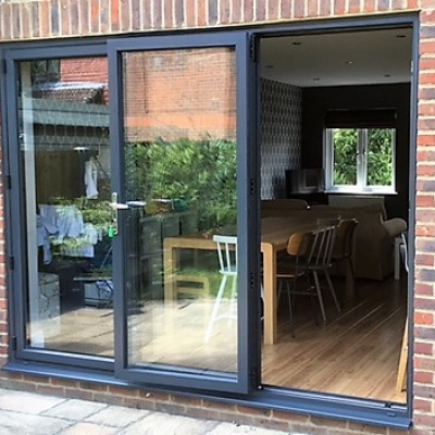 Image: 2017-06/anthracite-grey-3-pane-bifolding-door-with-traffic-door-open.jpg
