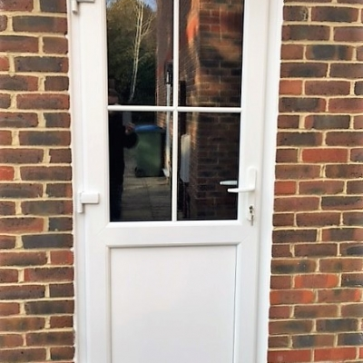 Image: 2017-12/emplas-optima-scultured-bead-garage-door-in-white-with-fixed-panel-to-bottom-and-georgian-astragal-bars-to-top.jpg