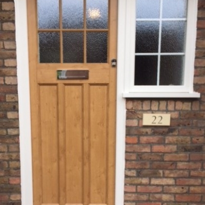 Image: 2018-05/boxmoor-front-door-with-adjacent-window.-door-in-evo-oak-with-white-frame.-minster-glazing.jpg