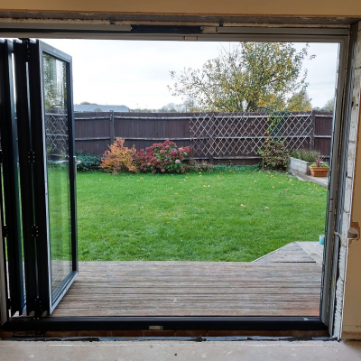 Image: 2018-11/3-pane-powder-coated-aluminium-bifolding-door-in-anthracite-grey-with-satin-handles-fully-open-internal-view.jpg