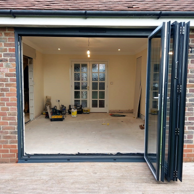 Image: 2018-11/3-pane-powder-coated-aluminium-bifolding-door-in-anthracite-grey-with-satin-handles-fully-open-stacked-to-the-right.jpg