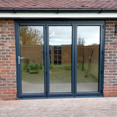 Image: 2018-11/3-pane-powder-coated-aluminium-bifolding-door-in-anthracite-grey-with-satin-handles.jpg