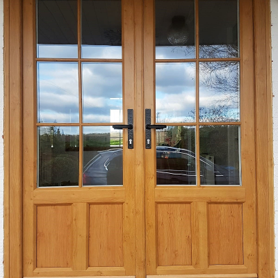 Image: 2018-12/1544783562_evolution-french-doors-in-evo-oak-woodgrain-finish-with-20mm-georgian-putty-ovolo-bars-with-timber-look-joints-and-black-wrought-iron-hardware.jpg