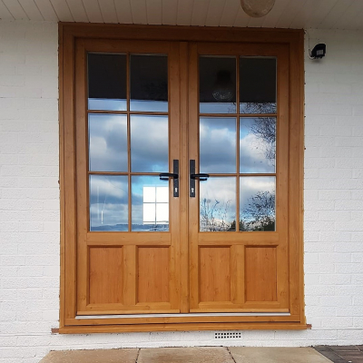 Image: 2018-12/evolution-french-doors-in-evo-oak-woodgrain-finish-with-20mm-georgian-putty-ovolo-bars-with-timber-look-joints-and-black-wrought-iron-hardware2.jpg