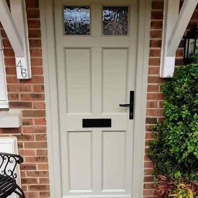Image: 2019-06/edc-timber-alternative-front-door-in-maple-design-in-olive-grey-with-black-wrought-iron-furniture-and-low-threshold-and-flemish-glazing.jpg