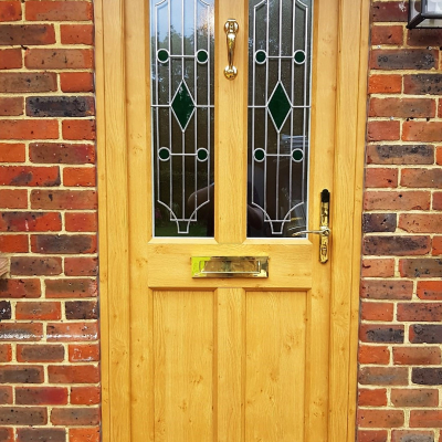 Image: 2019-08/ashwell-front-door-in-evo-oak-with-polished-brass-fittings-and-sf55-glazed-panels-with-green-jewels-backed-with-stippolyte-obscure-glazing.jpg