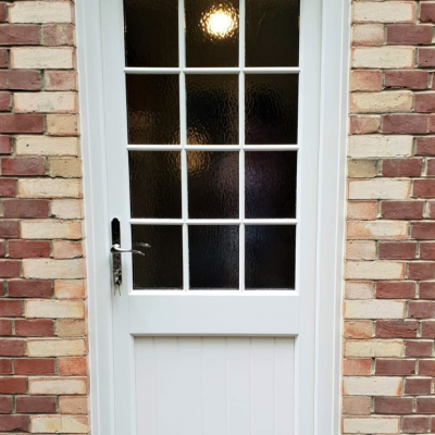 Image: 2020-01/shillington-back-door-in-cream-woodgrain-finish-with-minster-obscured-glazing-and-georgian-astral-bar-detail-with-regency-polished-chrome-hardware.jpg